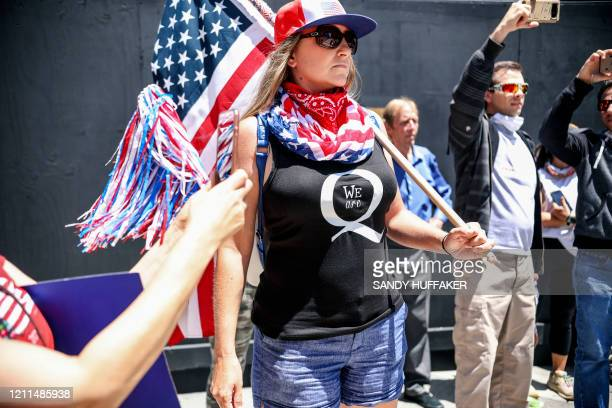 Conspiracy theorist QAnon demonstrators protest during a rally to reopen California and against StayAtHome directives on May 1 2020 in San Diego...