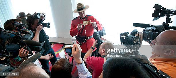 Constable Jeff Reid a counterfeit investigator for the Royal Canadian Mounted Police center displays a $C100 Canadian bank note for the media during...
