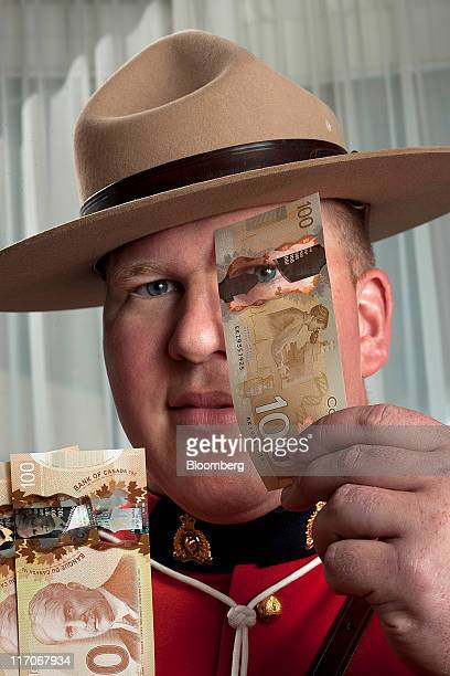 Constable Jeff Reid a counterfeit investigator for the Royal Canadian Mounted Police displays $C100 Canadian bank notes for a photograph in Toronto...