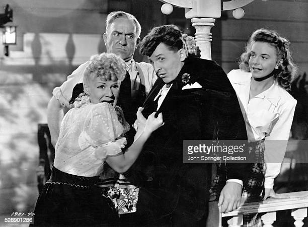 Constable Kockenlocker holds Norval Jones by the scruff of the neck while Trudy Kockenlocker grabs his blazer and Trudy's sister Emmy looks on The...