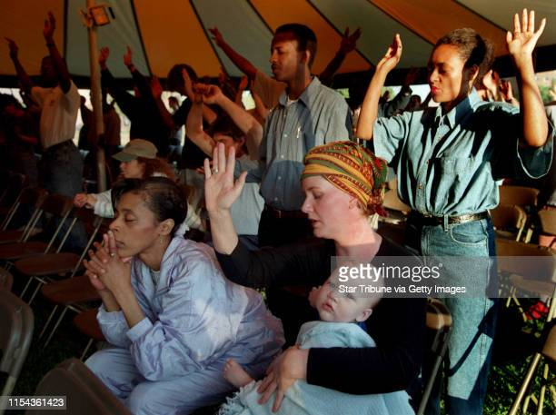 Constance Ballard left and Katherine Knopik with her son eight-month old son Samuel Knopik pray during tent revival services in Peavey Park Monday...