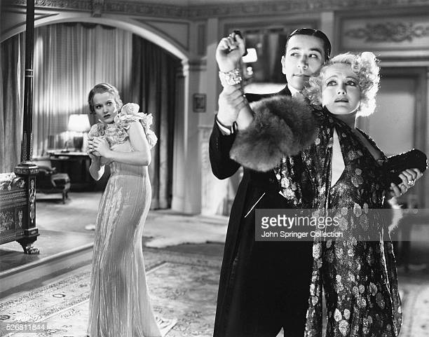 Constance Cummings as Jerry Healy looks on while George Raft as Joe Anton holds onto Mae West as Maudie Triplett in the 1932 film Night After Night