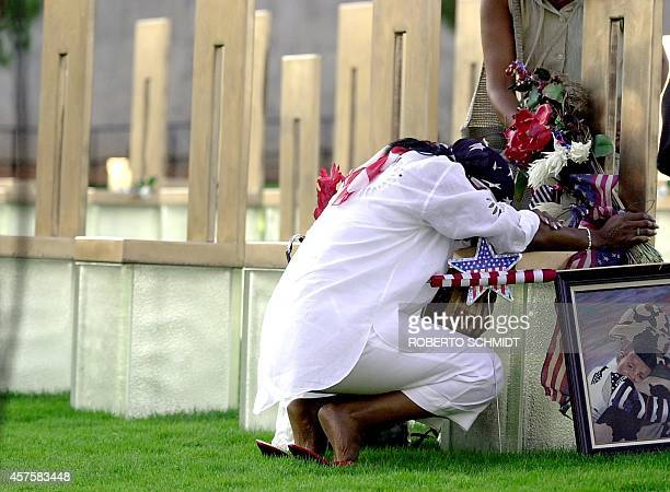 Constance Favorite the mother of bombing victim Lakecha Richardson prays in front of her daughter's chair in the Field of Empty Chairs sector of the...