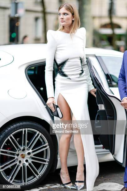 Constance Jablonski wears a white dress with embroidered stars and silver heels shoes outside the Vogue Foundation Dinner during Paris Fashion Week...