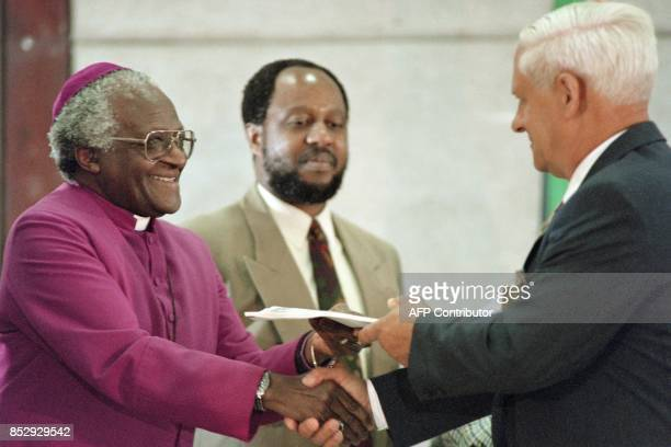 Constand Viljoen leader of the Afrikaansspeaking conservative Freedom Front hands over his party's submission to Desmond Tutu archbishop and head of...