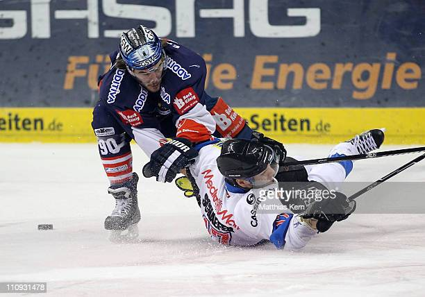 Constantin Braun of Berlin battles for the puck with Peter Schaefer of Ingolstadt during the third DEL quarter final playoff game between EHC...