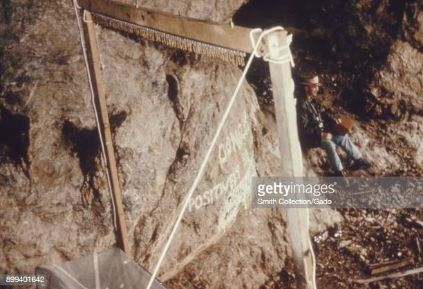 A Constantine bat trap placed in a cave with a man sitting on a rock in the back during an arbovirus field study 1974 Image courtesy Centers for...