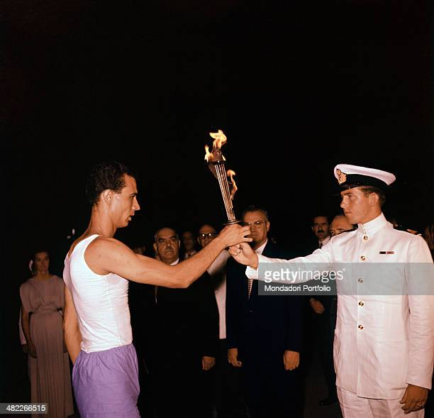 Constantine, Crown Prince of Greece, son of King Paul I, hands the Olympic torch to a cadet of the Italian Navy, during the relay of the Olympic...
