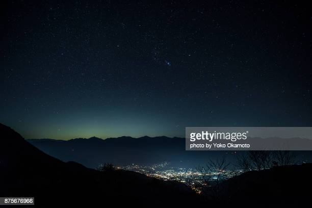 constellation orion and city light seen from senjojiki karl - noche fotografías e imágenes de stock