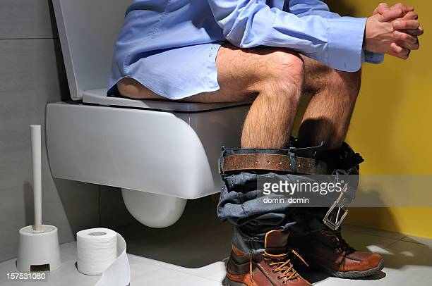 constipation, man is sitting on toilet bowl with pants down - men taking a dump stock pictures, royalty-free photos & images