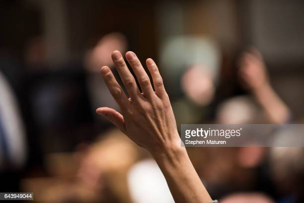 A constituent of Minnesota's 6th District raises their hand to ask a question of Rep Tom Emmer at a town hall meeting on February 22 2017 in Sartell...