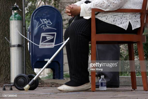 Constituent with a medical condition waits for her turn to speak during a news conference on postal service outside the Benjamin Franklin Post Office...