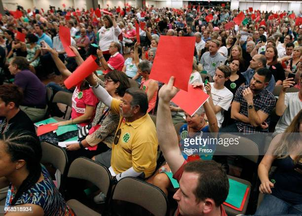 Constituents of U.S. Sen. Jeff Flake hold up signs in disagreement at a town hall event at the Mesa Convention Center on April 13, 2017 in Mesa,...
