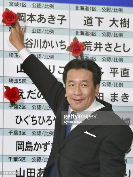 Constitutional Democratic Party of Japan leader Yukio Edano attaches a rosette to the name of a CDPJ candidate who is expected to win in the House of...