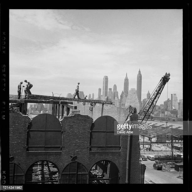 Constriction workers build a building with the Manhattan Skyline in the background in Brooklyn Heights, in March, 1958 in New York City, New York.