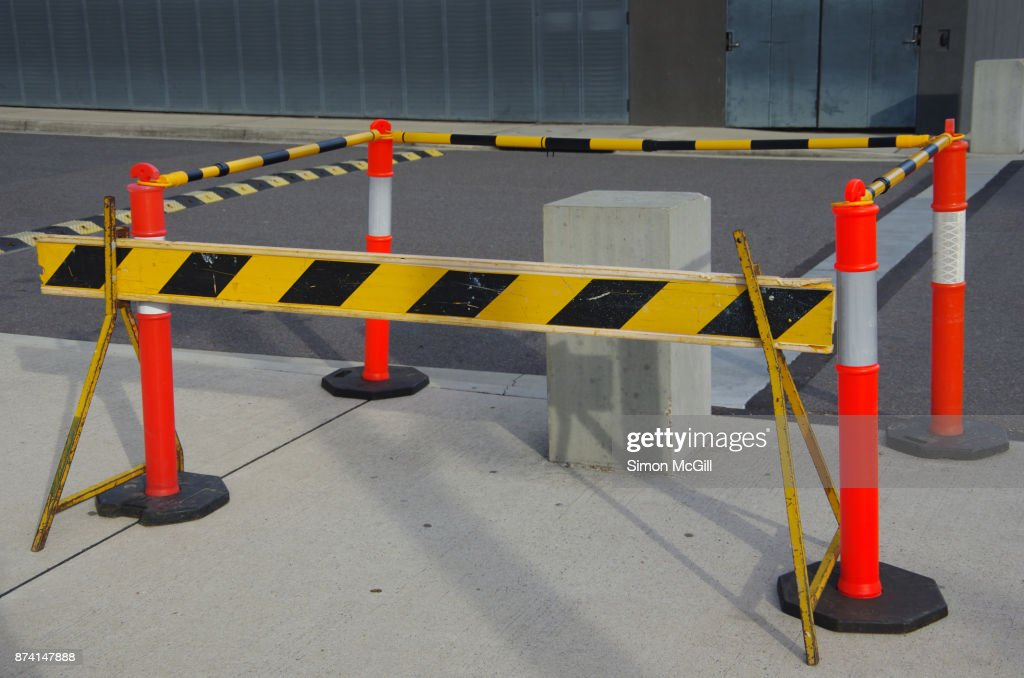 Construction barriers surround a concrete block under