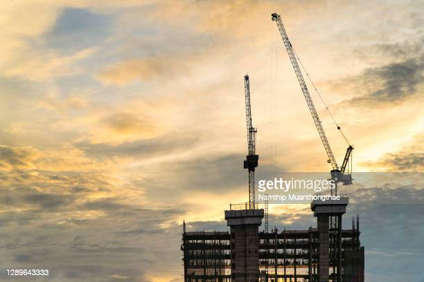 construction building and heavy cranes with the colorful sky of sunset time - south east asia stock pictures, royalty-free photos & images
