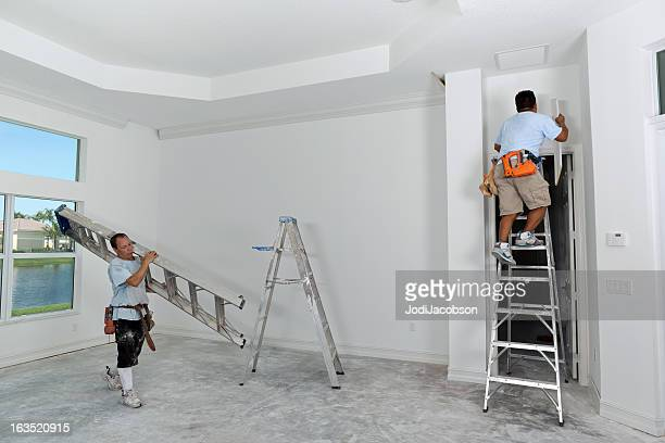 construction: carpenters installing crown moulding - crown molding stock photos and pictures