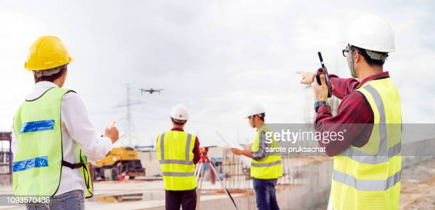 construction concept of engineer and architect working at construction site with drone over construction site. - drone photos et images de collection