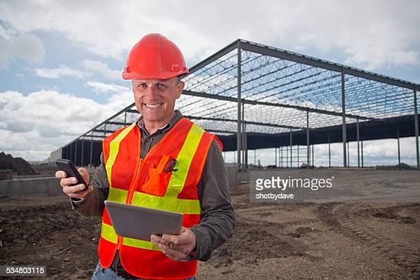 Contratista de construcción con la tableta y teléfono inteligente