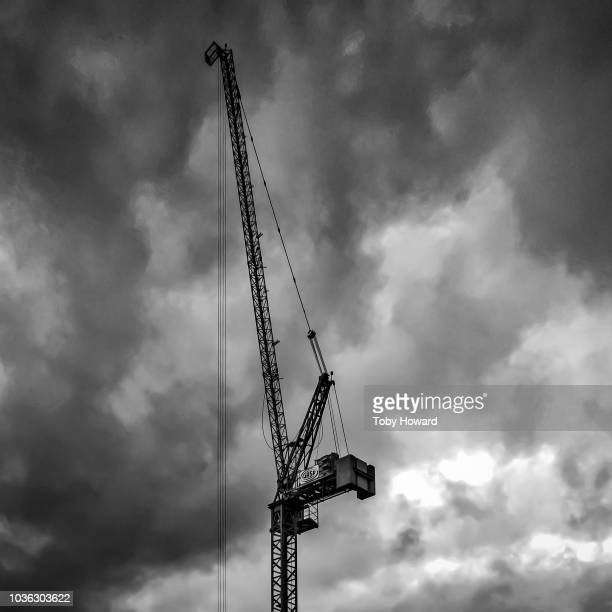 construction crane against dramatic sky - sail boom stock pictures, royalty-free photos & images