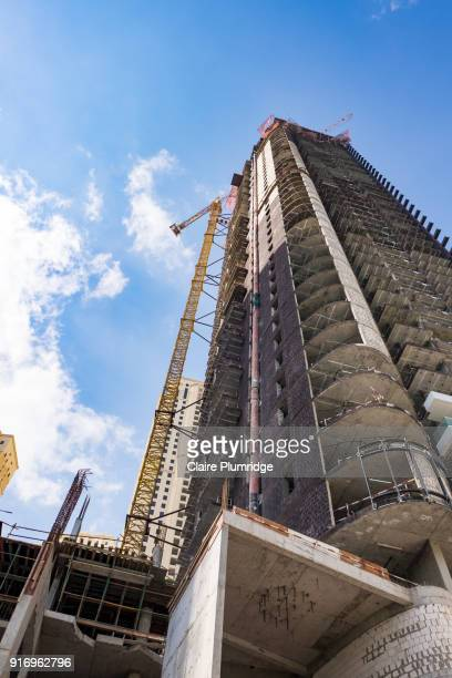 construction crane at the side of a building in dubai - taken from below looking up. - claire plumridge stock pictures, royalty-free photos & images