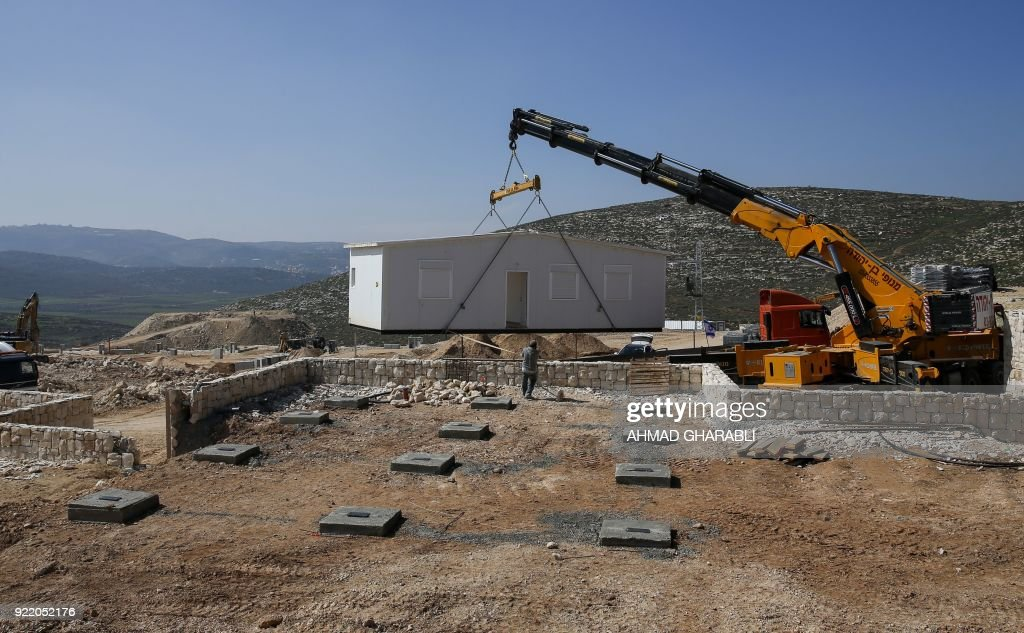 A construction crane installs new mobile homes in Amichai, the first new Israeli government-sanctioned settlement built in the Palestinian territories in some 25 years, mear the settlement of Shiloh, between the Palestinian cities of Ramallah and Nablus in the Israeli-occupied West Bank, on February 21, 2018, after the Israeli government decided to relocate there the settler families evicted from the wildcat outpost of Amona. /