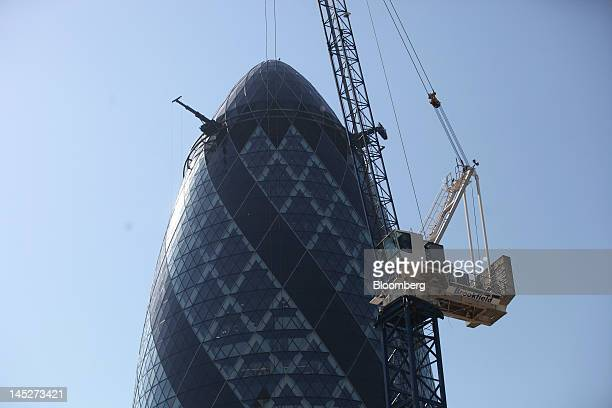 A construction crane is seen working on a building site alongside the Swiss Re Insurance building also known as 'the Gherkin' in the City of London...