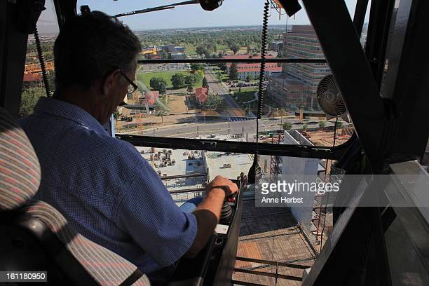 Construction crane operator Barry Benson looks at a parking structure 180 feet below that he's helping build at the University of Colorado Hospital...