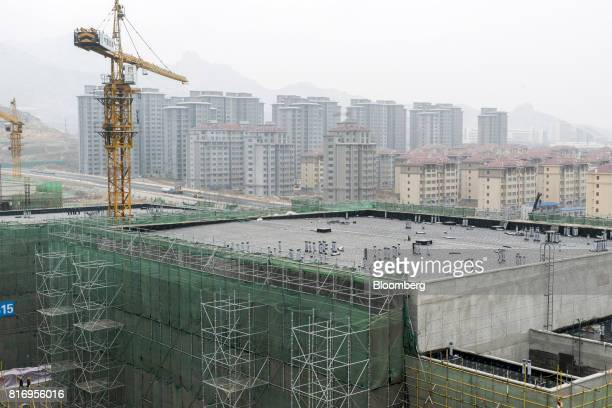 A construction crane rises above a commercial building under construction as residential buildings stand in the background inside the Dalian Wanda...