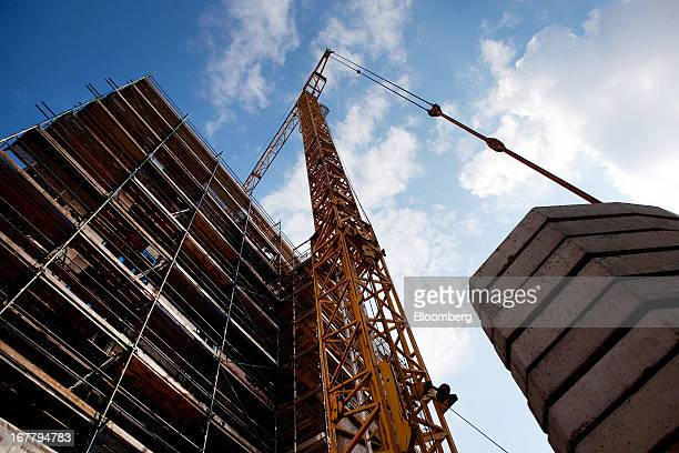 A construction crane stands over a block of residential housing on a building site located in the Mitte district of Berlin Germany on Monday April 29...