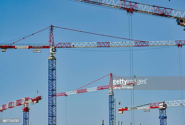 Construction cranes against a blue sky