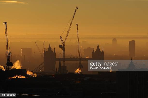 TOPSHOT Construction cranes are pictured near Tower Bridge in London at sunrise on January 18 2017 British business leaders welcomed Theresa May on...
