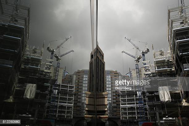 Construction cranes are reflected in the window of a neighboring building of the London Wall Place commercial property construction site in the City...
