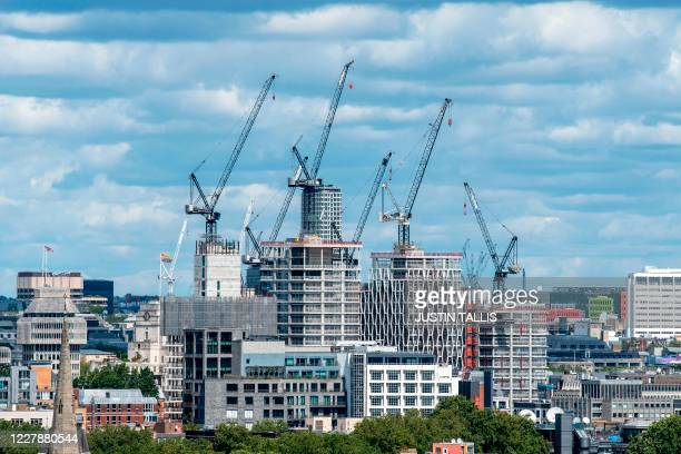 "Construction cranes are seen over development works in central London on August 2, 2020. - Plans for a shake-up of a ""complex and outdated planning..."