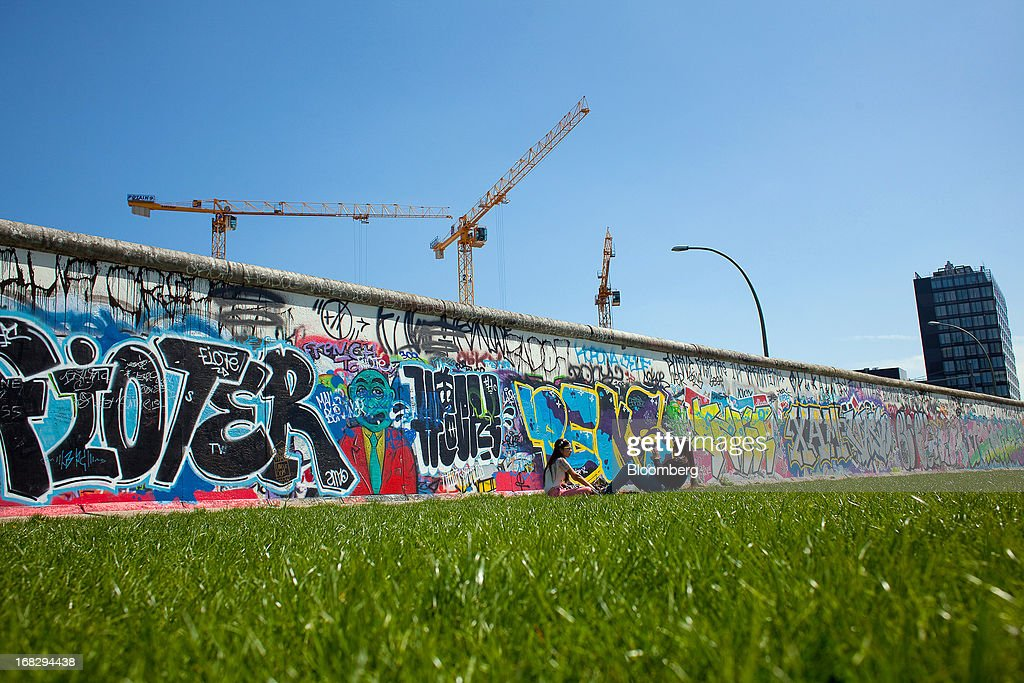 Construction cranes are seen rising from a building site above a section of the Berlin Wall's East Side gallery in Berlin, Germany, on Tuesday, May 7, 2013. Germany, Europe's largest economy, reported growth in the construction industry during April, according to Markit Economics. Photographer: Krisztian Bocsi/Bloomberg via Getty Images