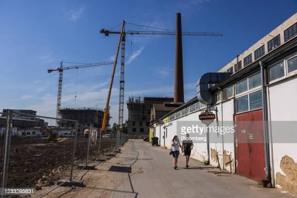 Construction cranes beside an inactive industrial chimney at a residential apartment construction site, on a plot of brownfield land in the Vysoany...