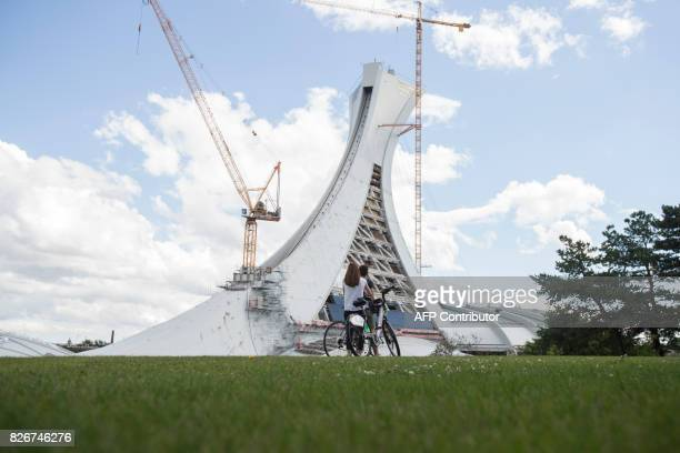 Construction cranes hang over on Olympic Stadium in Montreal Quebec August 5 2017 The stadium has been turned into a shelter for hundreds of refugees...