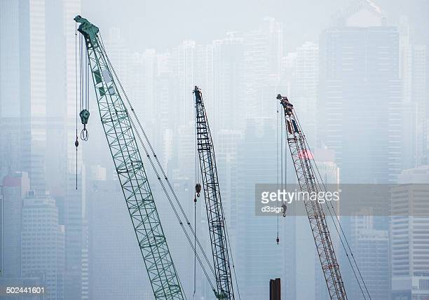 Construction cranes in front of Hong Kong skyline