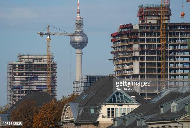 Construction cranes loom over new luxury apartment buildings under construction as the broadcast tower at Alexanderplatz stand behind on October 22...
