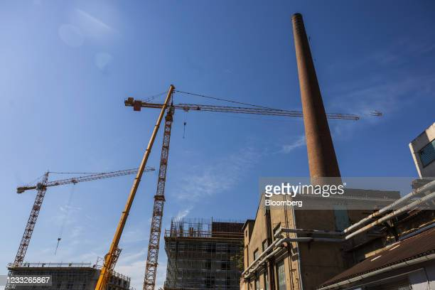 Construction cranes near an inactive industrial chimney at a residential apartment building site, on a plot of brownfield land in the Vysoany...