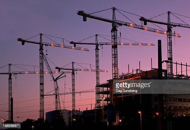 Construction cranes on a building site at night