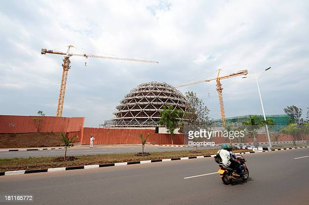 Construction cranes operate at the site of the Kigali Convention Center part funded by the Bill and Melinda Gates Foundation in Kigali Rwanda on...