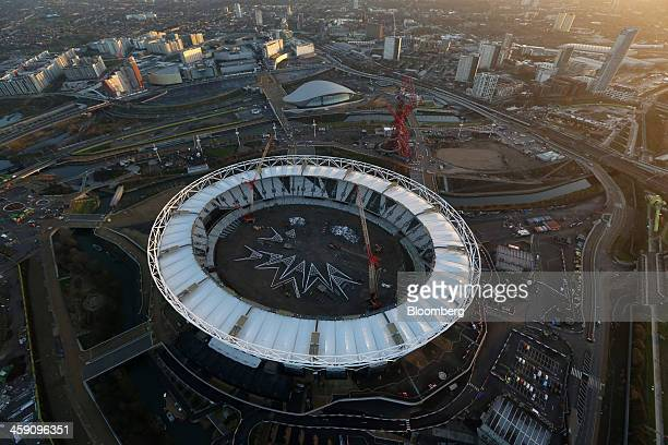 Construction cranes operate inside the London 2012 Olympic Stadium in this aerial photograph looking over the Queen Elizabeth Olympic Park towards...