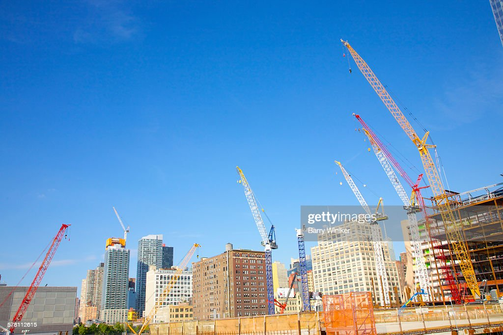 Construction cranes reaching to blue sky, NYC : Stock Photo