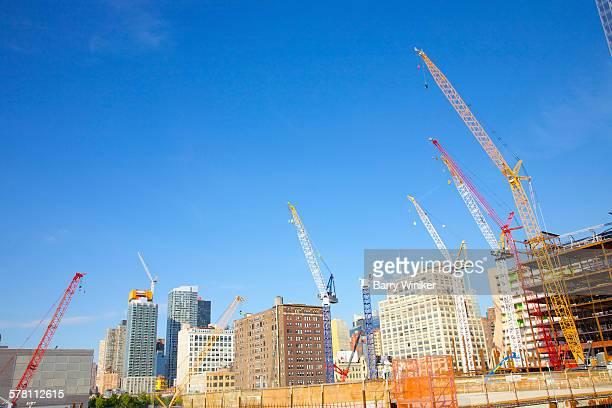 Construction cranes reaching to blue sky, NYC