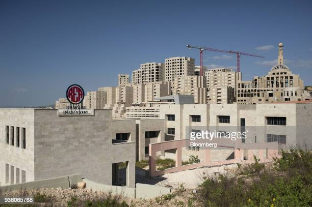 Construction cranes stand above buildings in the new Palestinian city of Rawabi West Bank on Sunday March 25 2018 As the transfer of the US embassy...