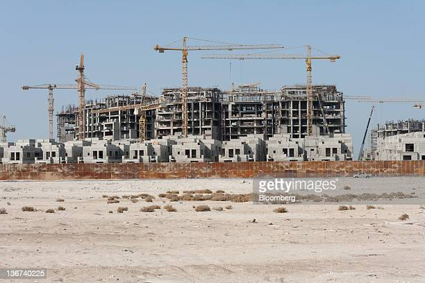 Construction cranes stand amongst unfinished buildings at the ADISC residential leisure and commercial compound in Abu Dhabi United Arab Emirates on...