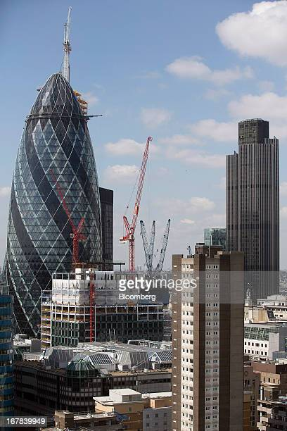 Construction cranes stand in front of the Swiss Re building also known as 'the Gherkin' left and Tower 42 right in the City of London UK on Tuesday...
