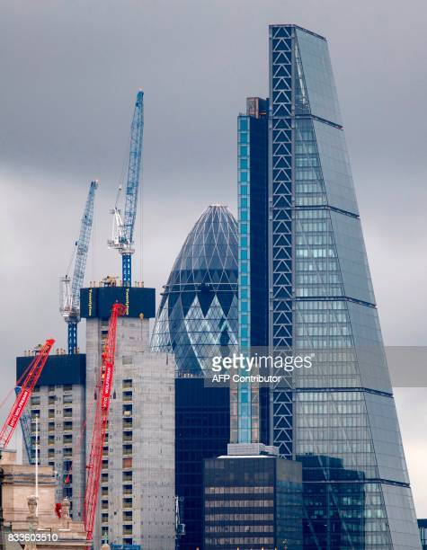 Construction cranes stand near skyscrapers in the City of London including 30 St Mary Axe commonly called the 'Gherkin' and the Leadenhall Building...